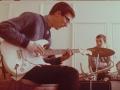 Hank repeteert backstage met zijn nieuwe witte Fender Stratocaster in 1963 samen met Brian Bennett.