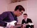 Hank repeteert backstage met zijn nieuwe witte Fender Stratocaster in 1963 samen met Bruce Welch.