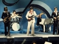 The Shadows op de Eurovisiecontest in Stockholm 1975. Hank Marvin lead, Bruce Welch bas, John Farrar gitaar, Brian Bennett drums en Alan Tarney aan de vleugel.