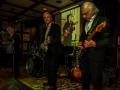 Reunie Back to Tilburg, middagoptreden Guitar Syndicate, met op de achtergrond de foto van de eerste rhythm gitarist Marc Vandermeulen (RIP).
