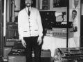 Dick Denney ( (1921-2001), gitarist en chief engineer van JMI, met een vroege flat-fronted PA versterker Metal Clad MC50-6 in 1964 op de Musical Instrument Industries Trade Fair in het Russell Hotel London. De unit rechts boven op de PA is een Page-Boy office PA mixer (Audio Frequency Amp met geheugen).