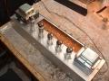 Achterzijde chassis met buizen sectie Vox V15 combo. 2 Eindbuizen EL84, preamp met 1*ECC81 en 2*ECC83. Deksel boven printplaat verwijderd.