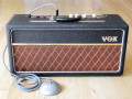 Vox Echo Reverberation Unit in  Basketweave 1964, Red panel met witte ronde knoppen, plastic MK III handle, Brass vents.  Vox logo rechts boven en Vox footswitch in Stamped Round Metal uitvoering (plaatstaal).